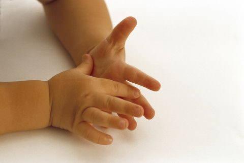 Младенец рассматривает свои руки